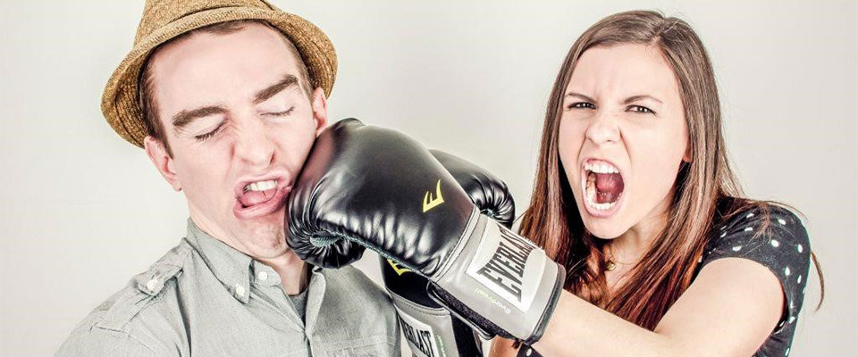 Woman punching a man with a boxing glove