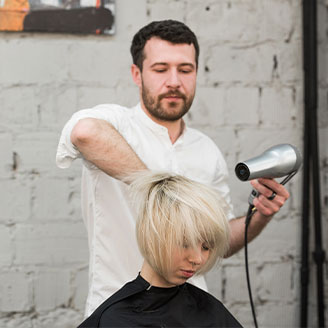 Man giving a woman a blow dry